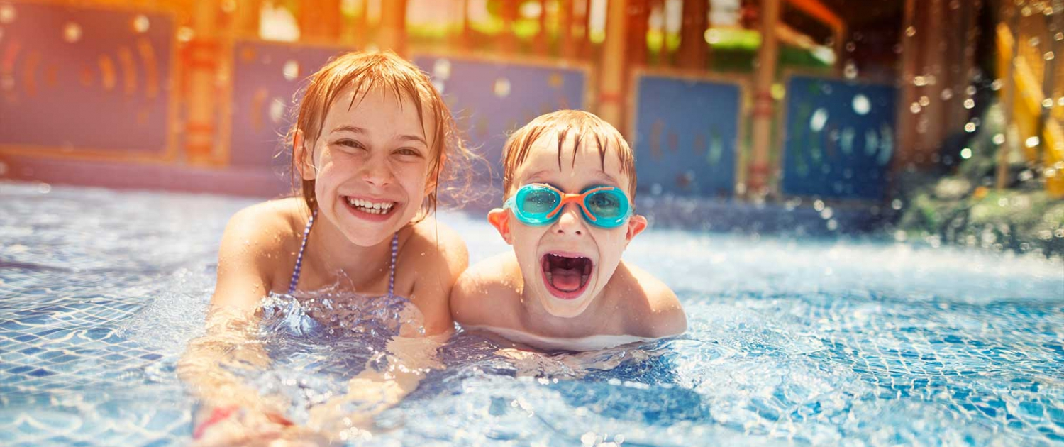 Girl and boy playing in a public swimming pool
